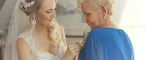 An image of a bride helping her grandma get ready on her wedding day; taken from one of our Toronto Wedding Videorgraphy videos