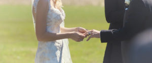 Image of a wedding couple placing eachothers rings at their vineyard ceremony; taken from one of our Toronto Wedding Videorgraphy videos