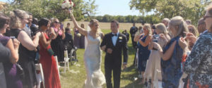An Image of a wedding couple walking down the aisle as husband and wife at a vineyard; taken from one of our Toronto Wedding Videorgraphy videos