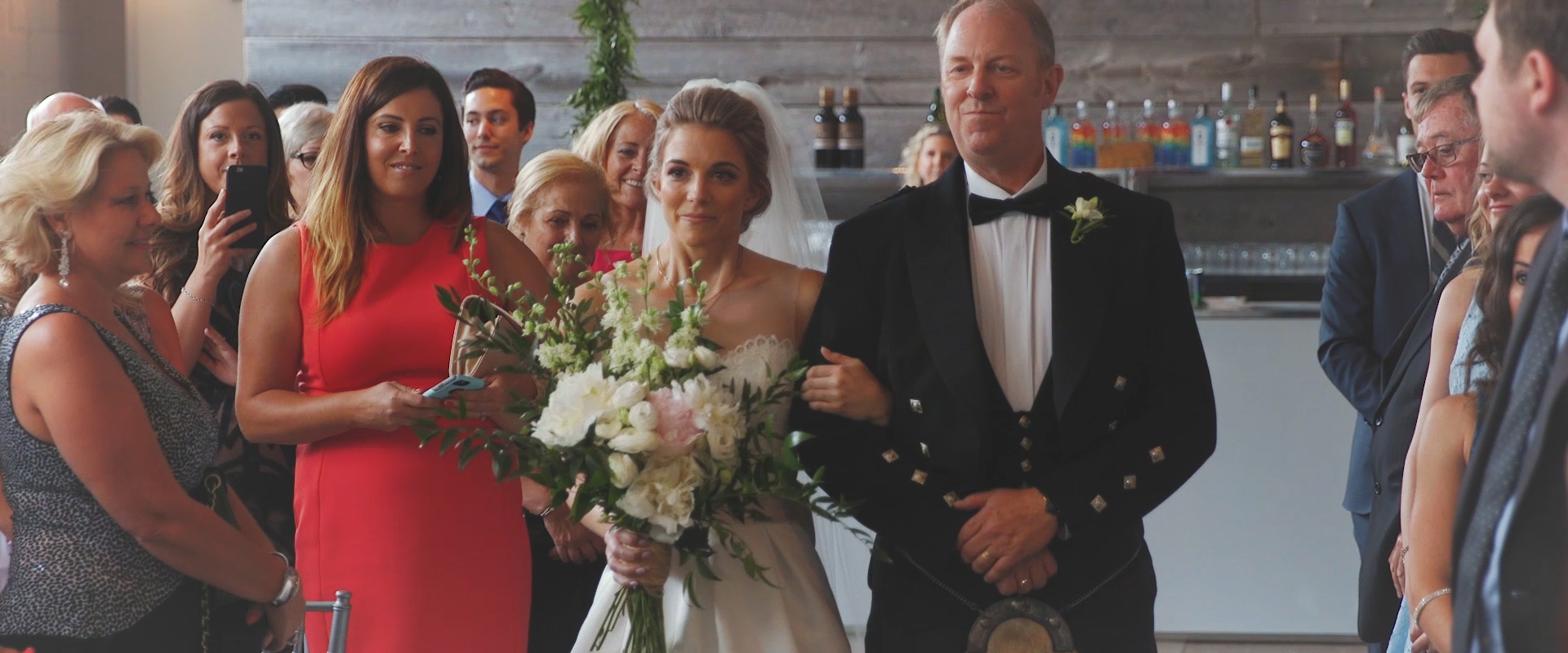 An image of a father walking his daughter down the aisle at her wedding ceremony; taken from a Toronto Wedding Video