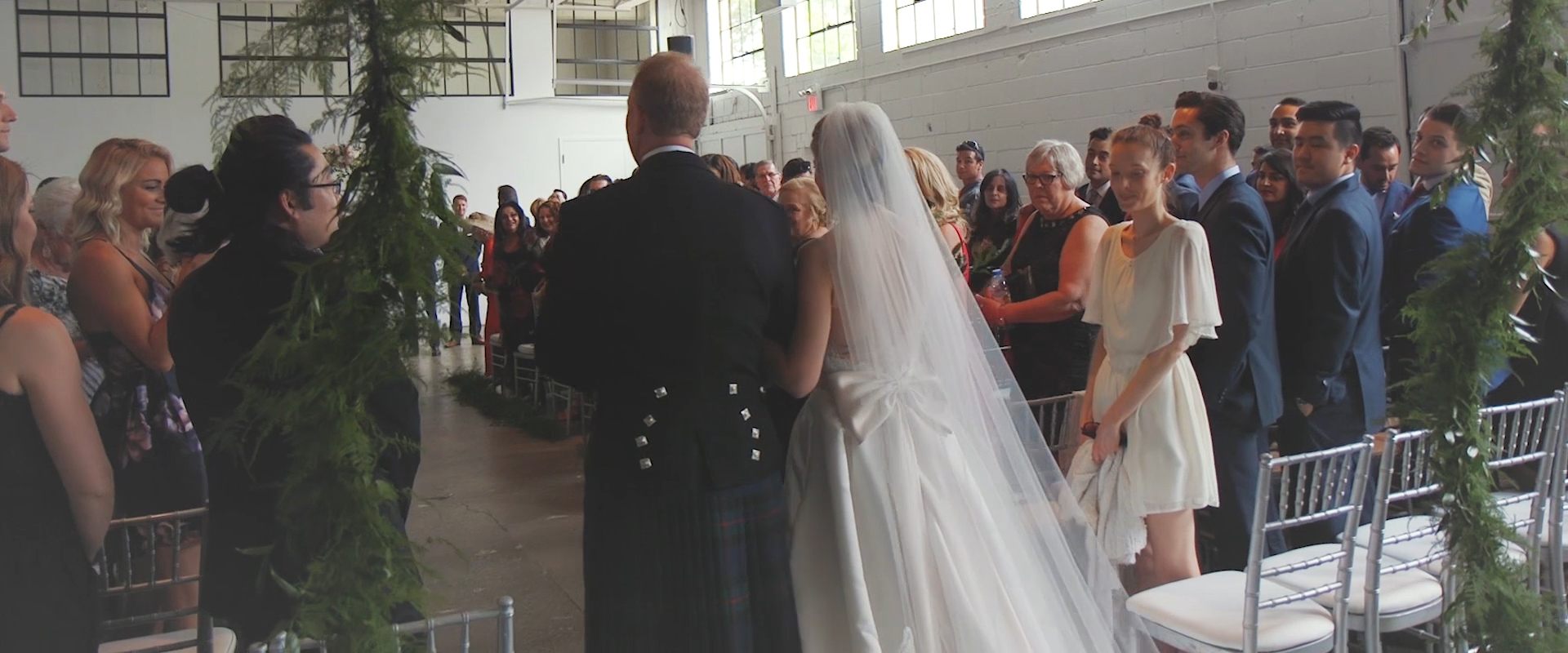 An image of a father walking his daughter down the aisle to be wed; taken from a Toronto Wedding Video