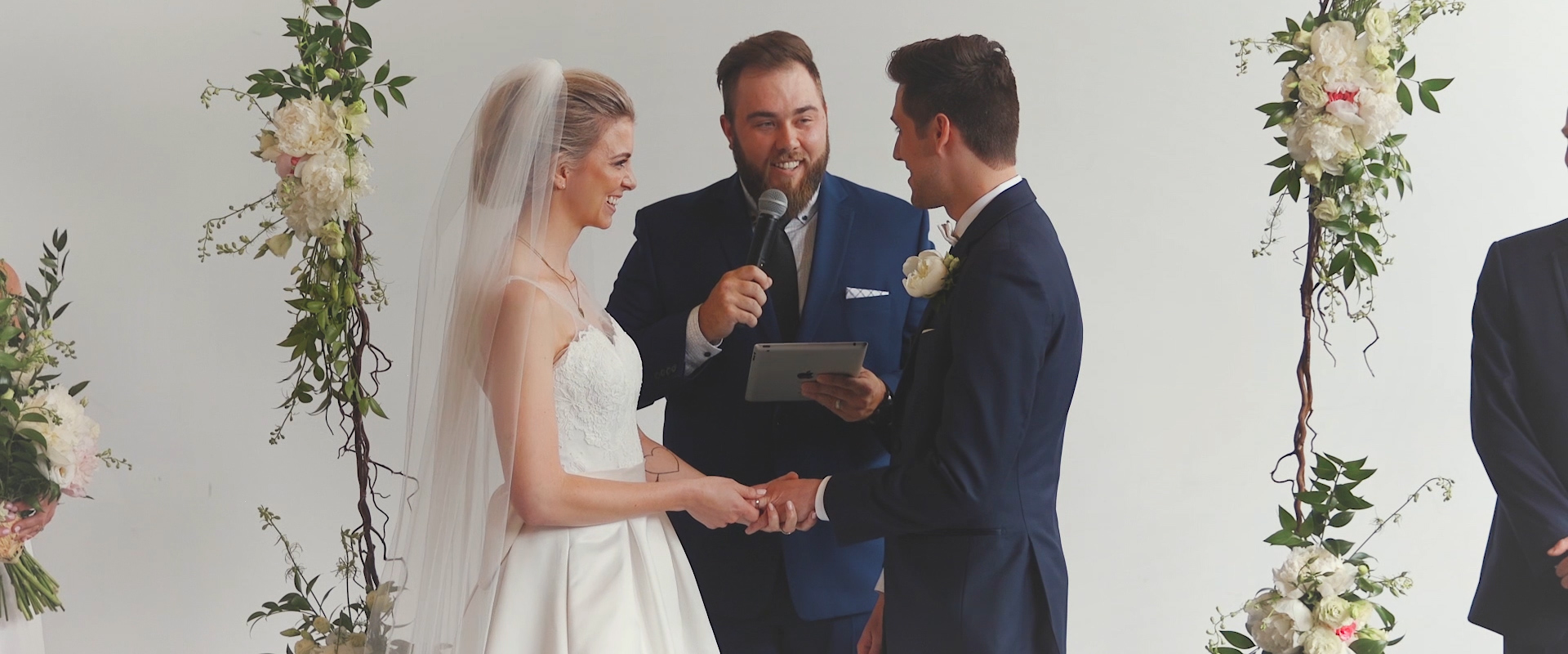 An image of a bride and groom placing each others rings at their wedding ceremony; taken from a Toronto Wedding Video