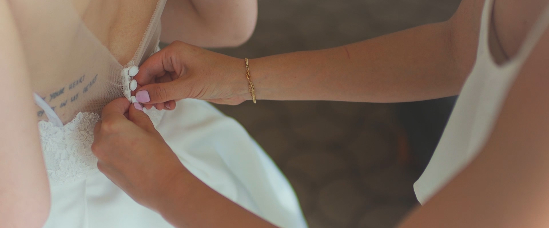 An image of a bridesmaid helping her bride button up her dress; taken from a Toronto Wedding Video