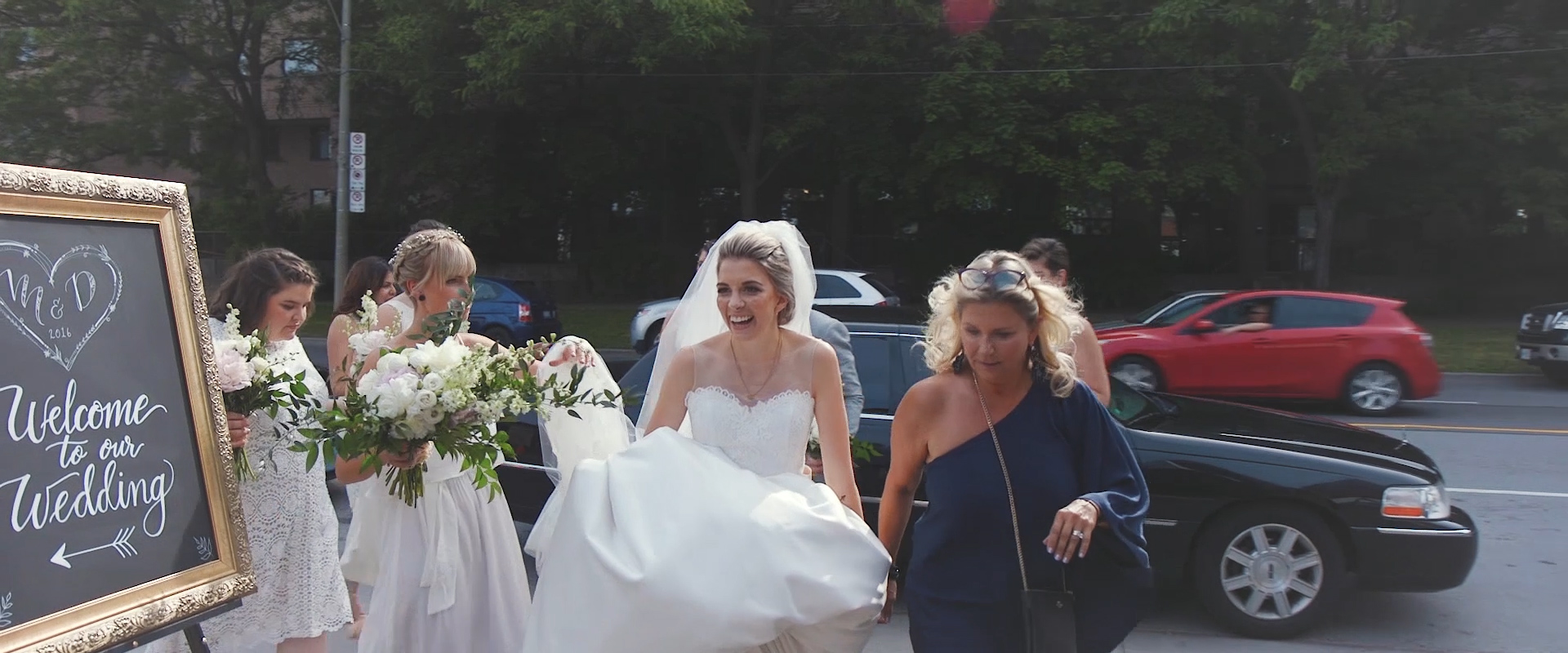 An image of a bride walking into her reception hall on her wedding day; taken from a Toronto Wedding Video