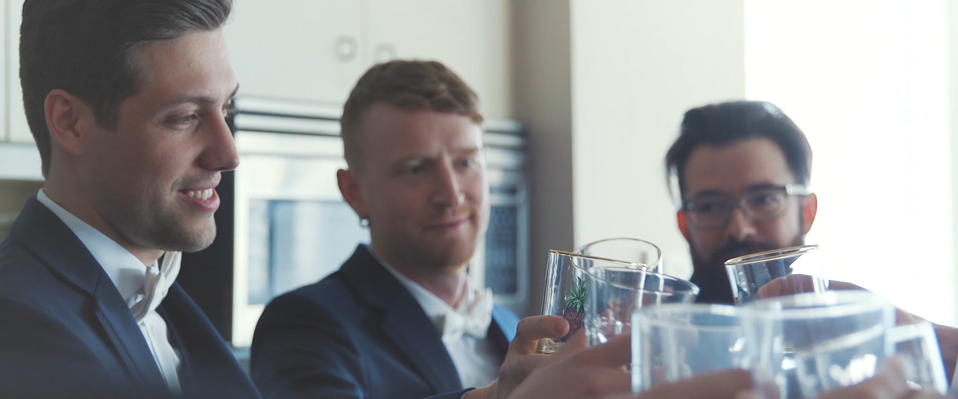 An image of a groom sharing a drink with his groomsmen on his wedding day; taken from a Toronto Wedding Video