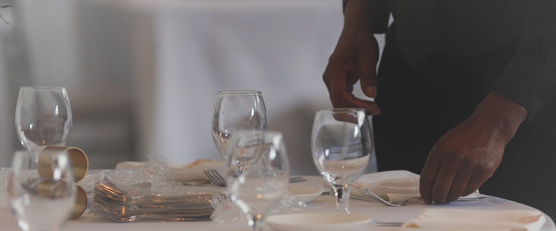 An image of a table being set at a wedding reception; taken from a Toronto Wedding Video