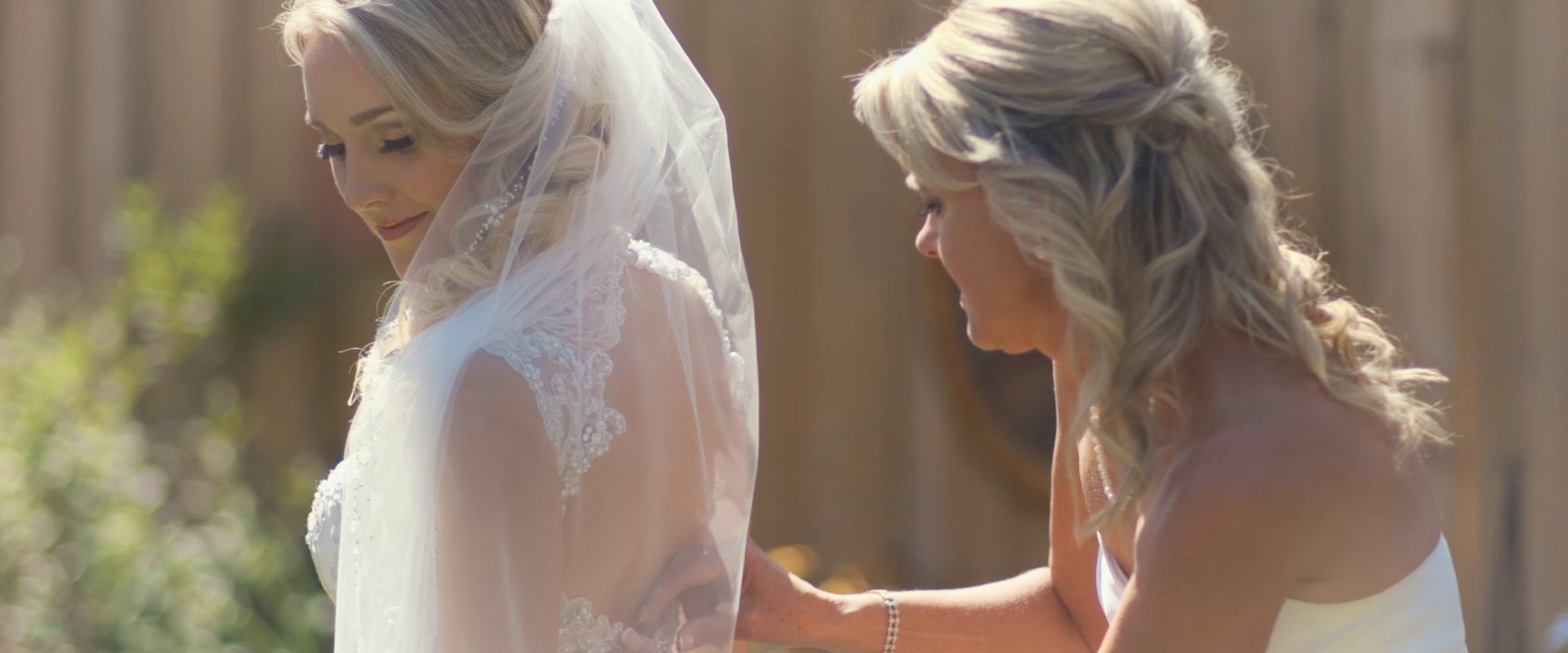 An image of a mother helping her daughter with her wedding dress on the day of her wedding; taken from a Toronto Wedding Video