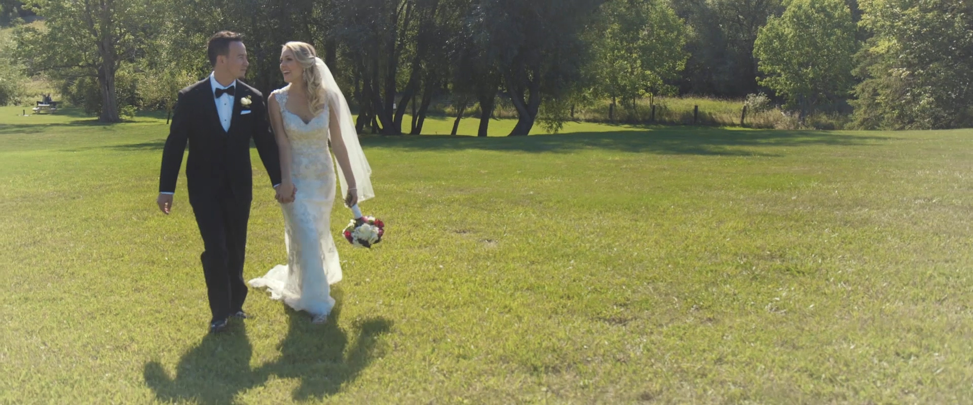 An image of a bride and groom walking on a vineyard on their wedding day; taken from a Toronto Wedding Video
