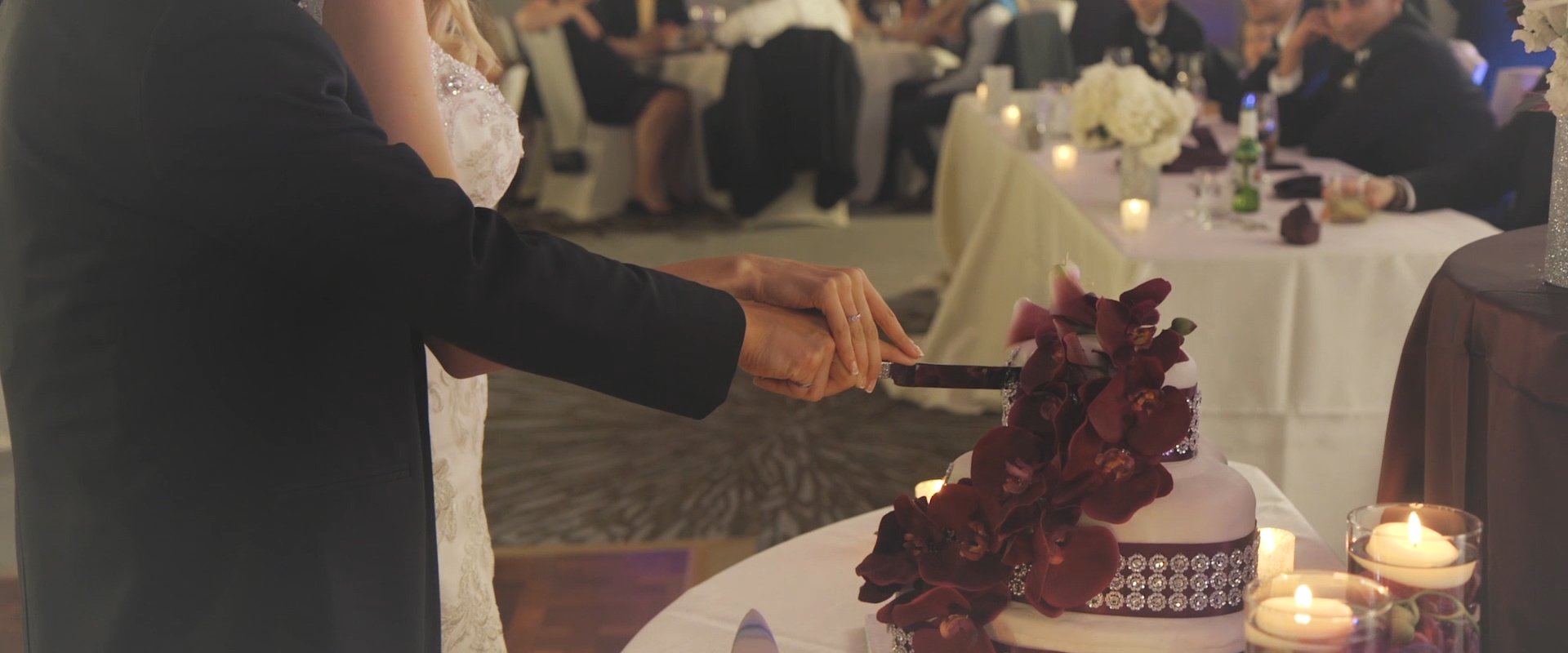 An image of a bride and groom cutting their wedding cake; taken from a Toronto Wedding Video