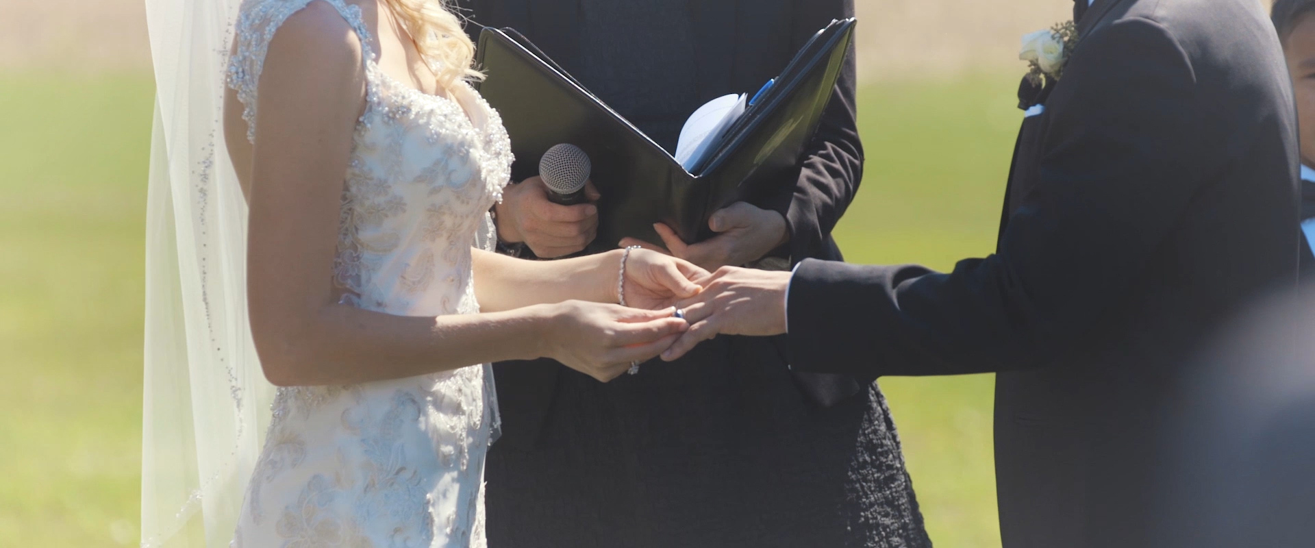 An image of a bride placing a ring on her grooms finger during their wedding ceremony in collingwood; taken from a Toronto Wedding Video
