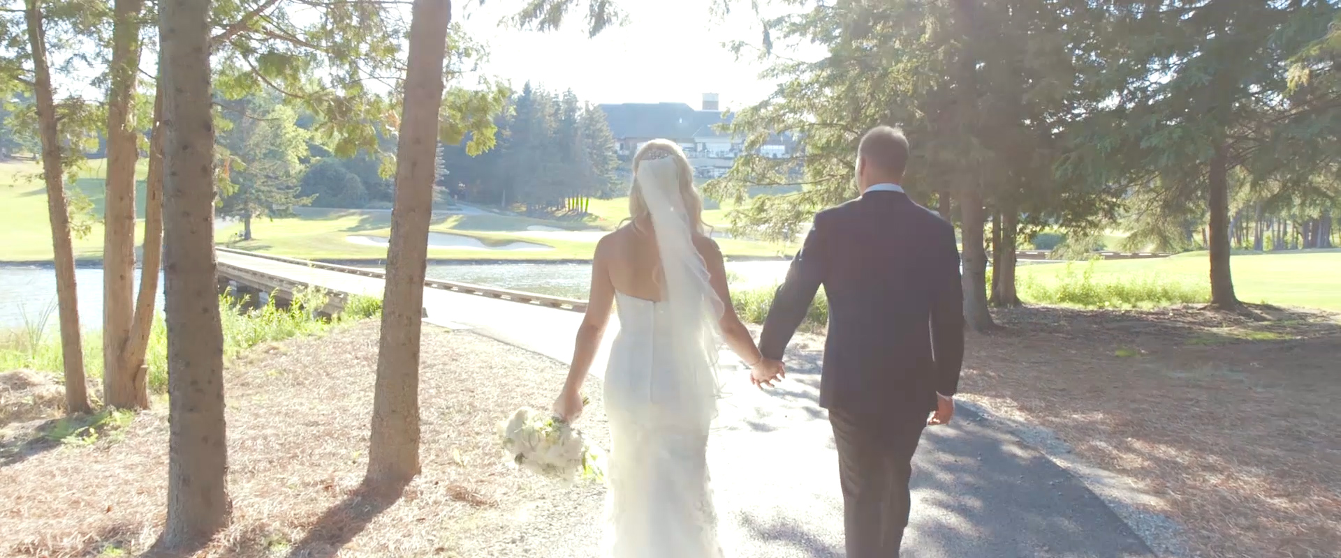 An image of a bride and groom walking down a path at King Valley Gold course; taken from a Toronto Wedding Video
