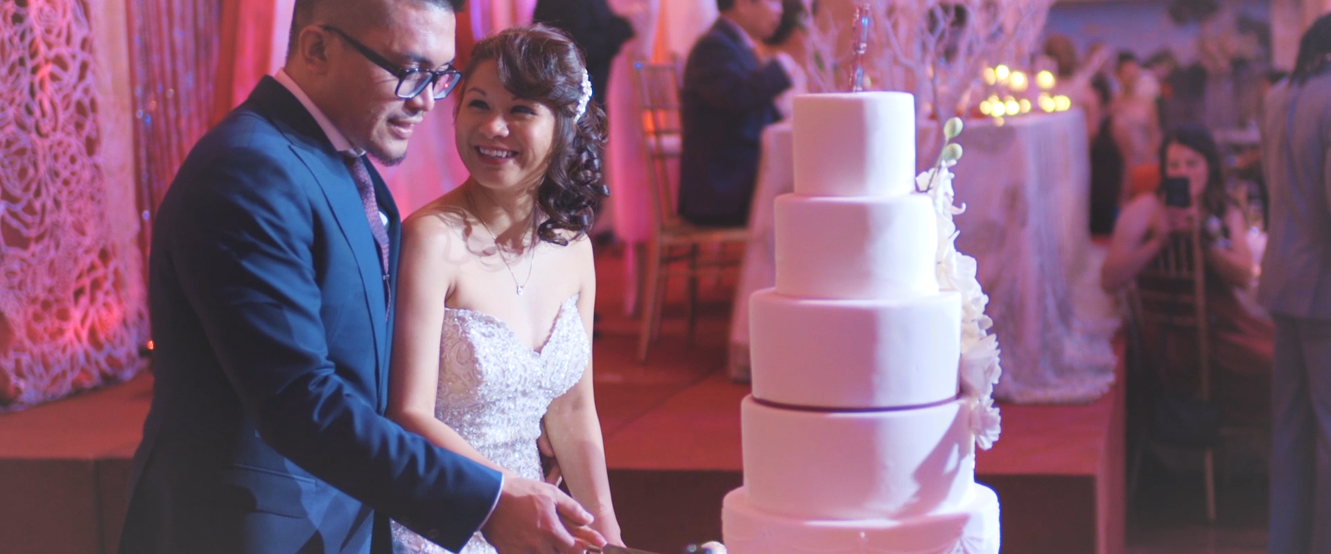 An image of a couple cutting their cake at their wedding reception; taken from one of our Toronto Wedding Videos