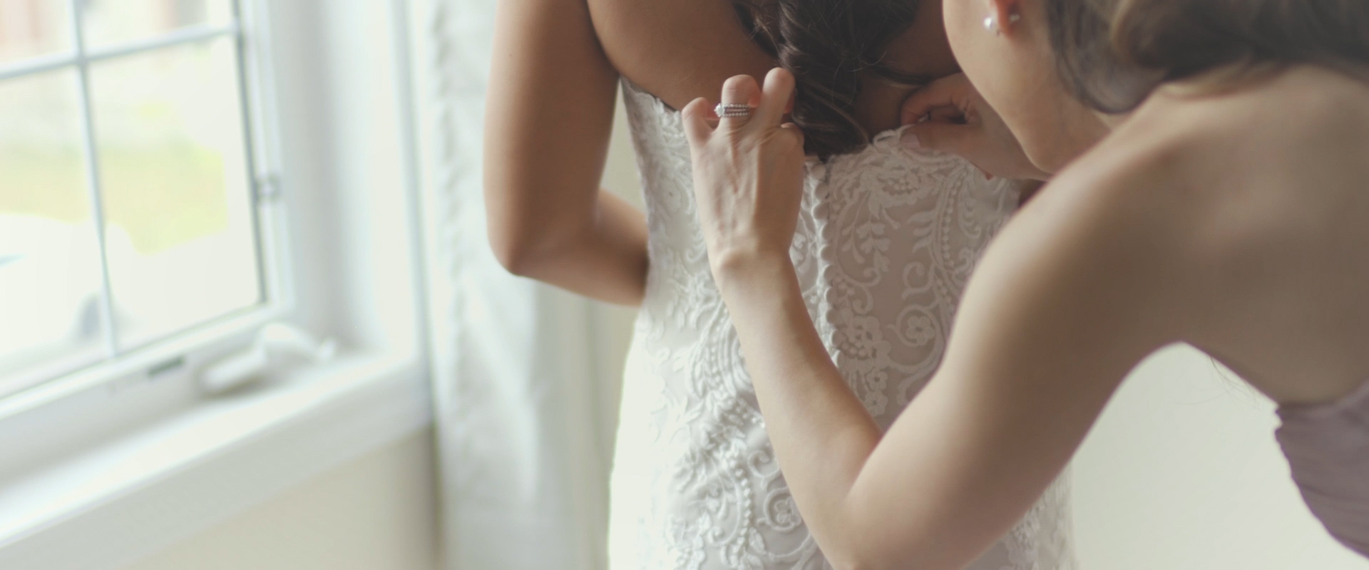 An image of a bridesmaid helping her bride with her dress on her wedding day; taken from a Toronto Wedding Video