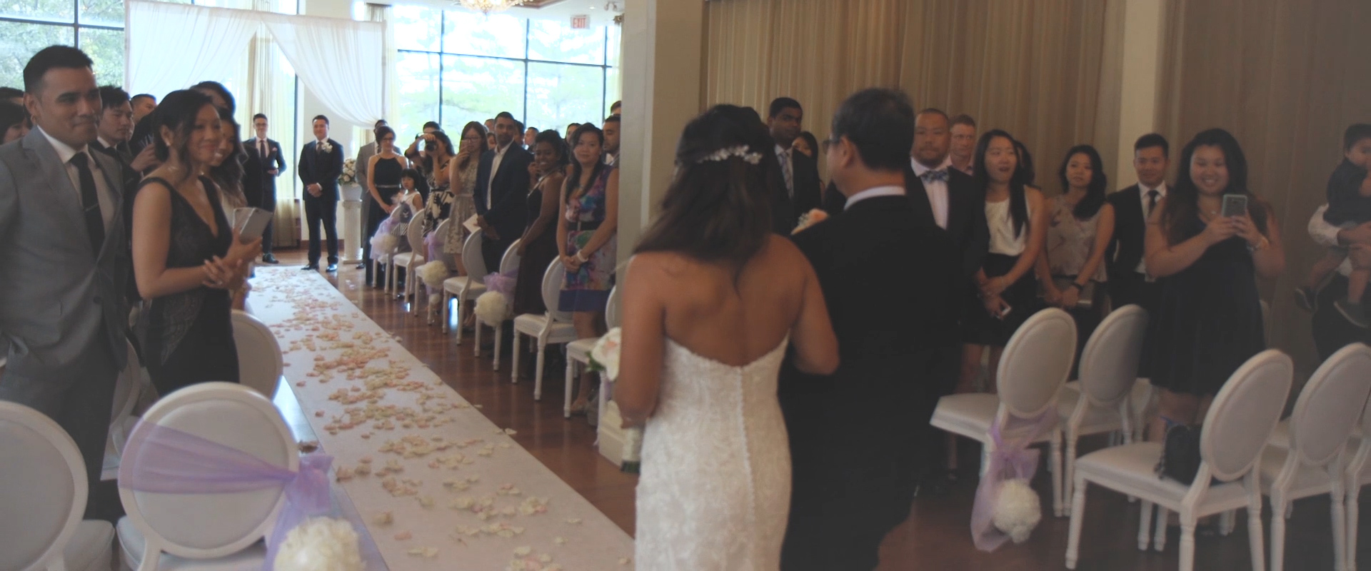 An image of a bride being walked down the aisle by her father at her wedding ceremony; taken from a Toronto Wedding Video
