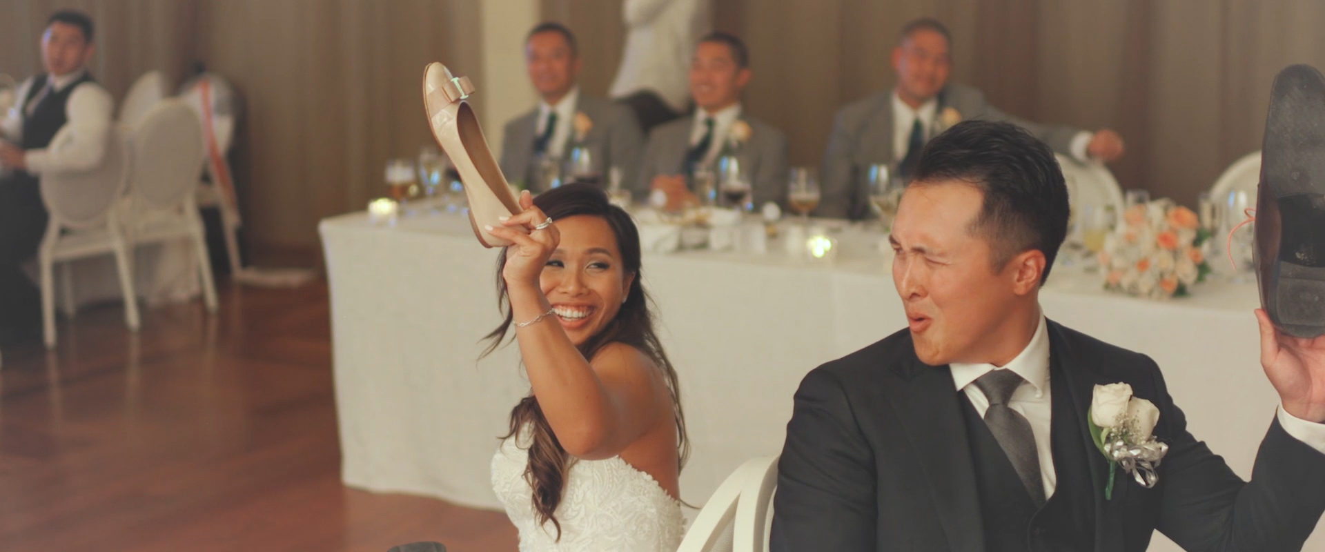 An image of a bride and groom playing the shoe game during their wedding reception; taken from a Toronto Wedding Video