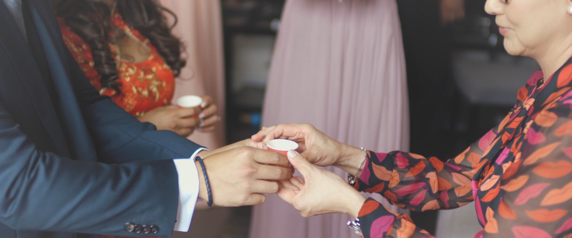 An image of a groom and mother during a traditional tea ceremony on his wedding day; taken from a Toronto Wedding Video