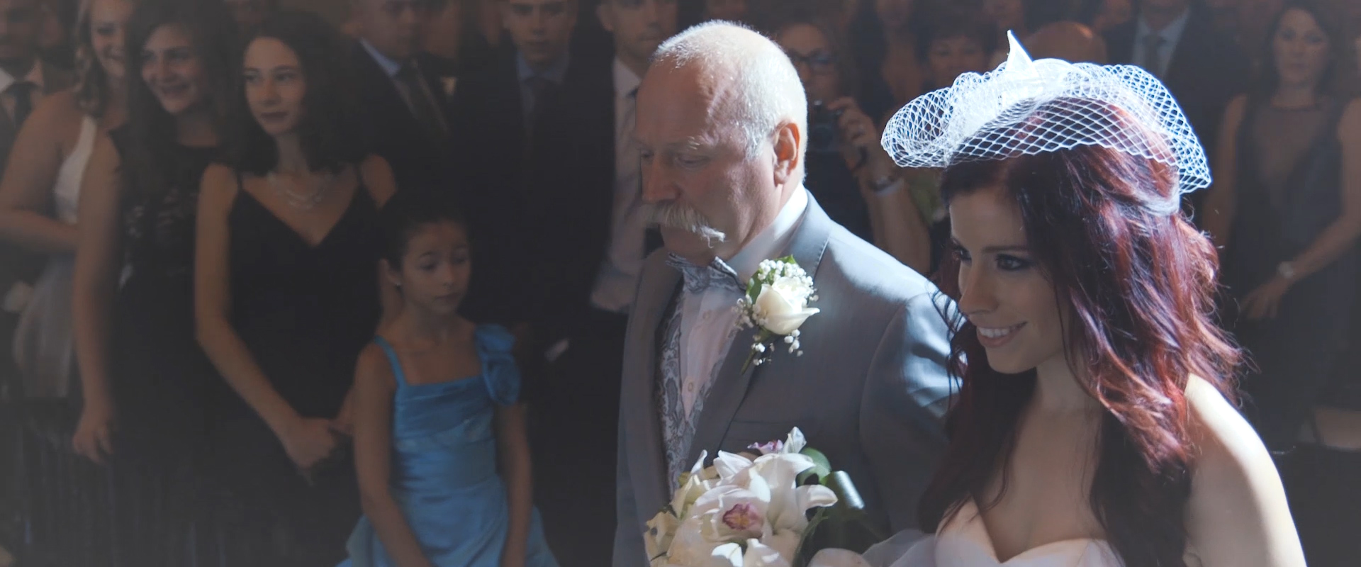 An image of a bride being walked down the aisle by her father; taken from a Toronto Wedding Video