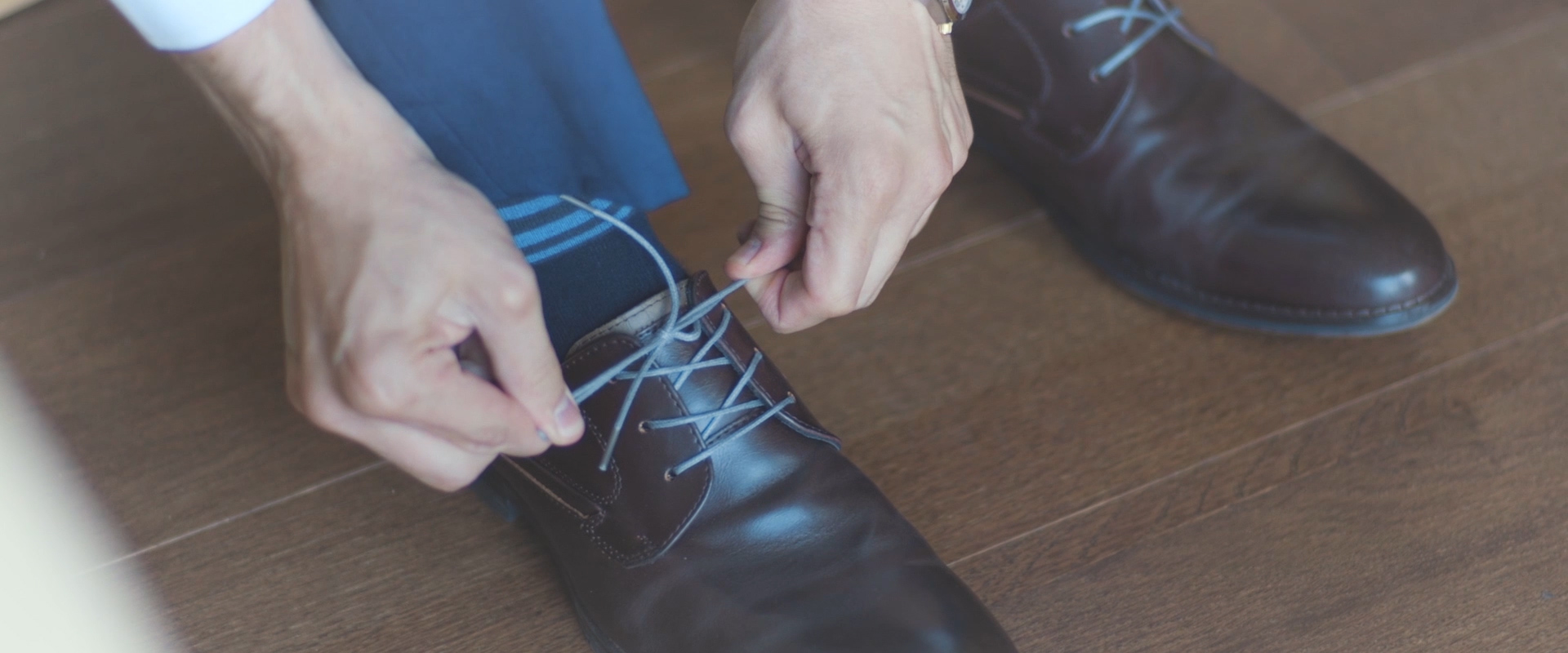 An image of a groom putting his shoes on; taken from a Toronto Wedding Video
