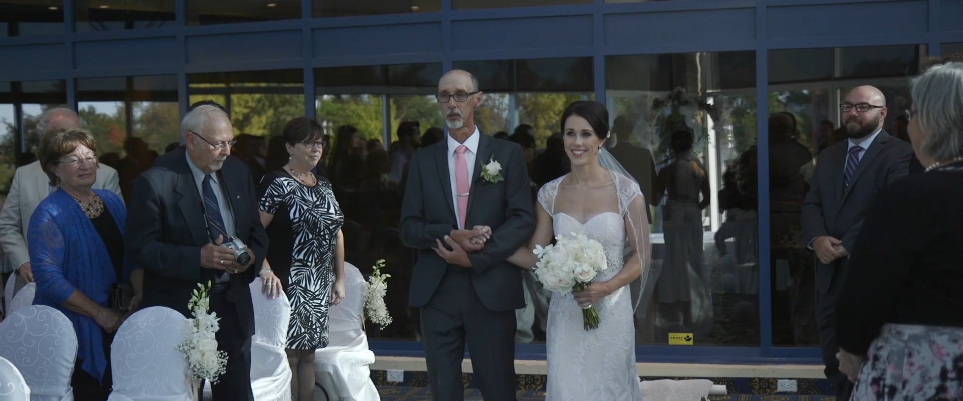 Image of a bride walking down the aisle at Lionhead golf course; taken from one of our Toronto Wedding Videography videos